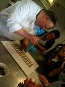 Chocolatier aan het werk met dompel bonbons